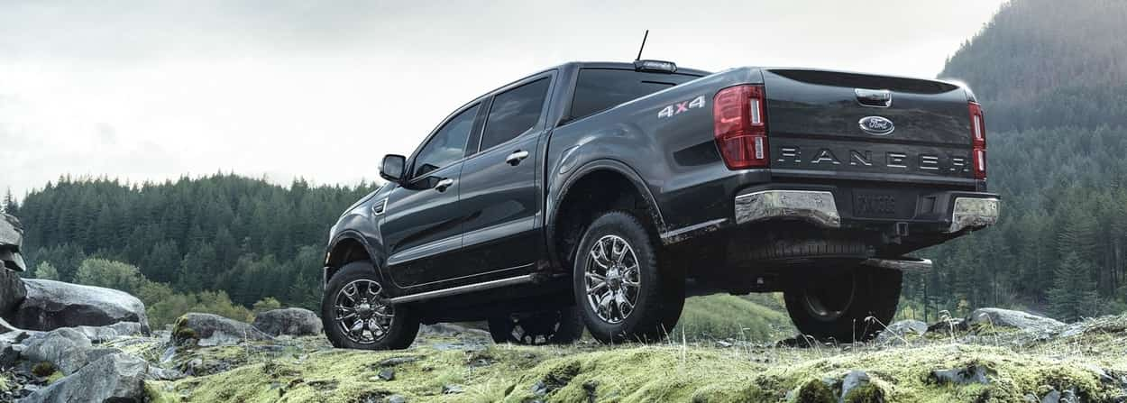 2019 Ford Ranger on rocky hill top with its driver sitting on a nearby rock overlooking a lake