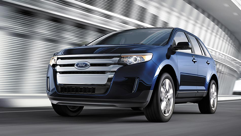 2014 Ford Edge LTD driving beside a building