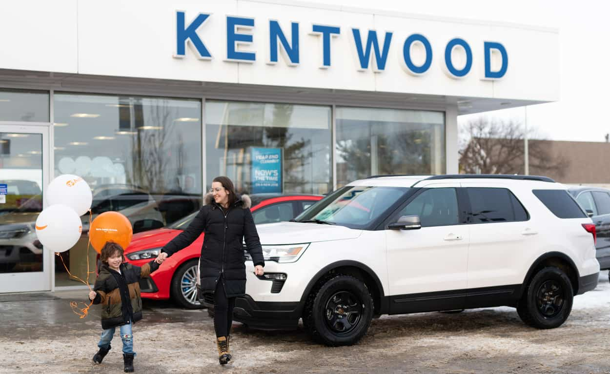 Kira Paran and her son holding balloons while walking outside the Kentwood Ford entrance and white Ford Explorer in the background