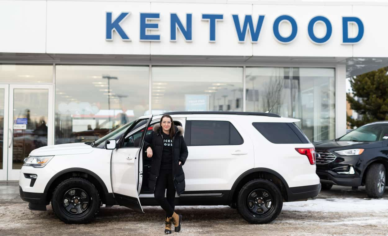 Kira Paran standing in front of the Kentwood Ford entrance and white Ford Explorer