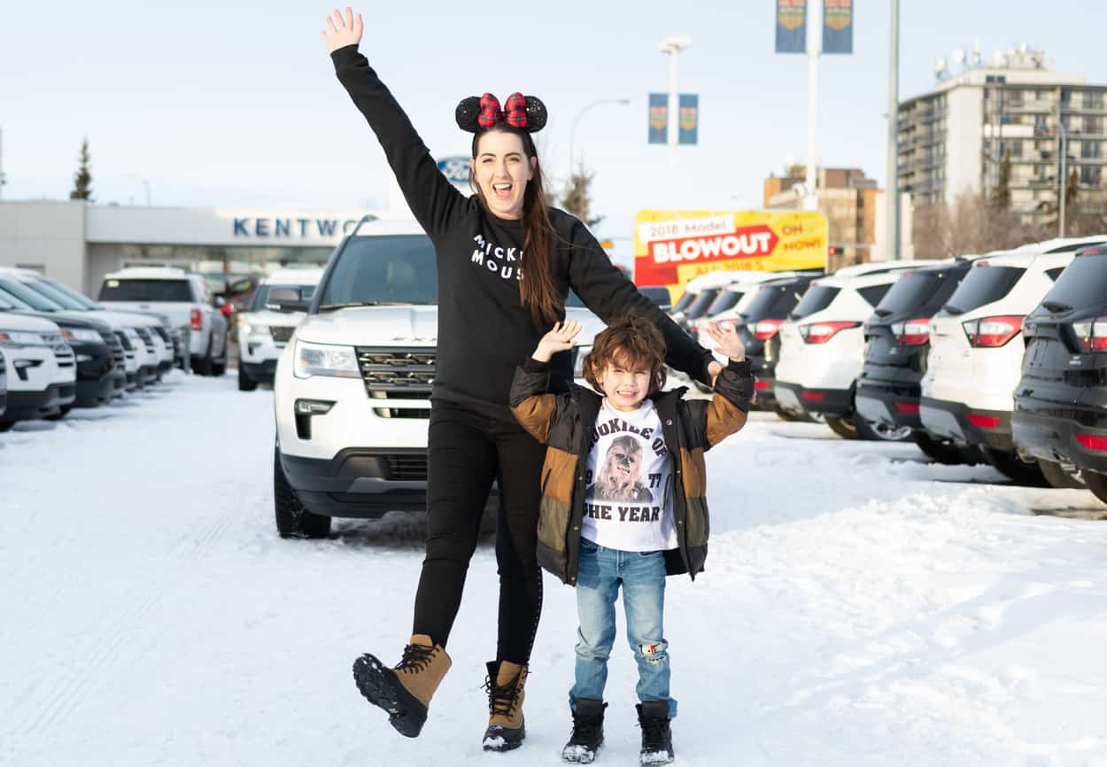 Kira Paran and her son holding hands happily in front of a white Ford Explorer
