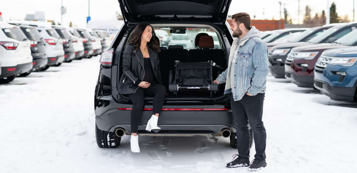 Lyndsey SMith and husband posing with the liftgate of the Ford Edge