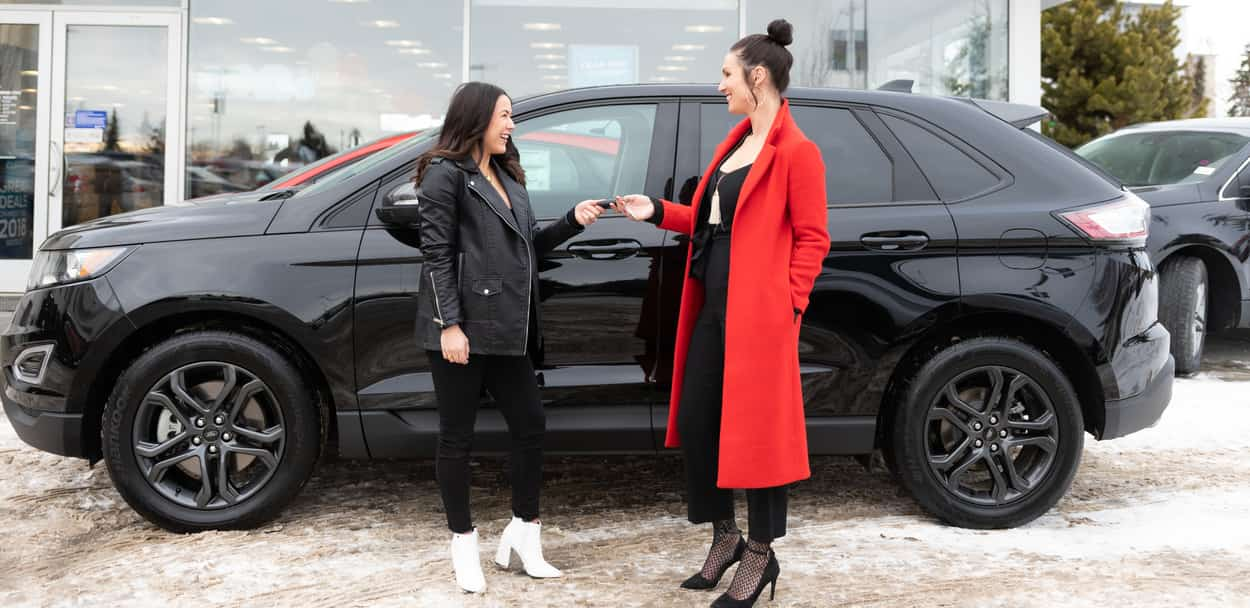 Lyndsey Smith and some lady in a red jacket asking each other stuff in front of the Ford Edge