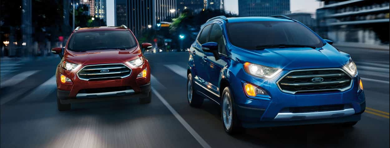 Two Ford EcoSports driving in the night; one red, one blue