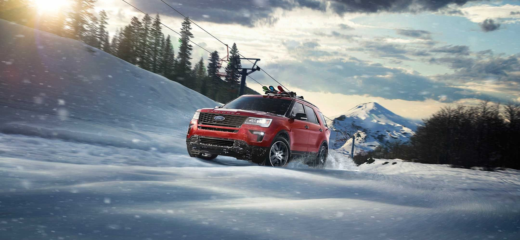 2019 ford explorer in red, driving through snow with roof rack
