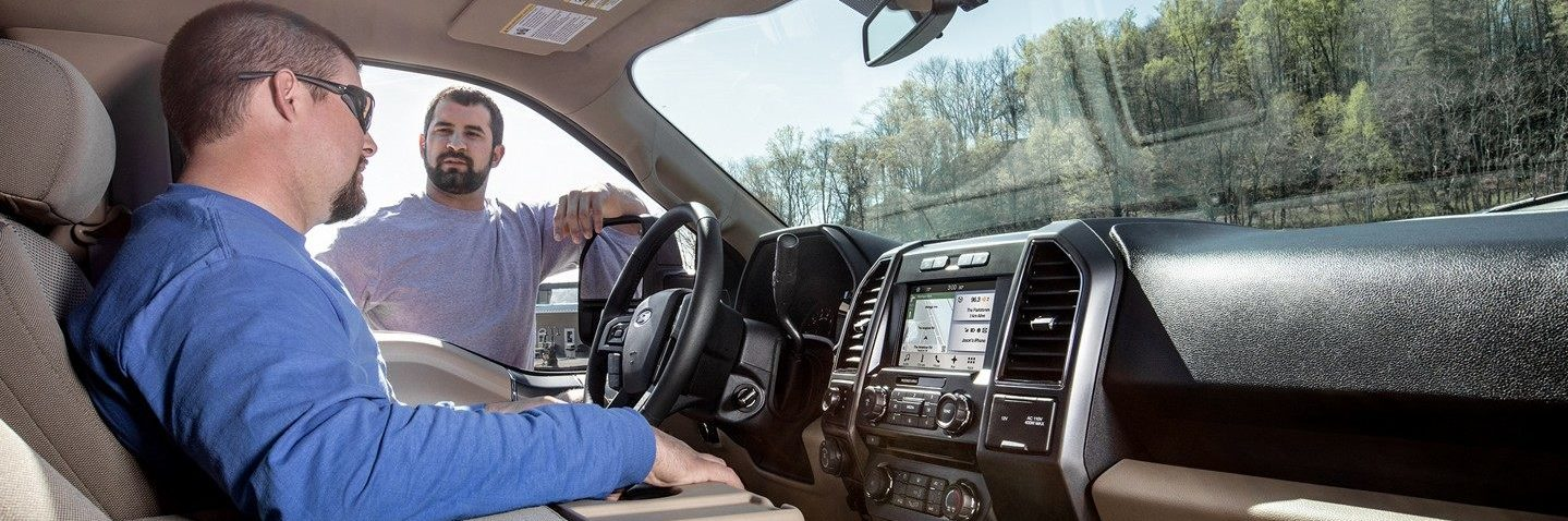 interior shot of man in blue long sleeve shirt sitting in the ford f-150 drivers seat while talking to man at the drivers side window in lavender t shirt
