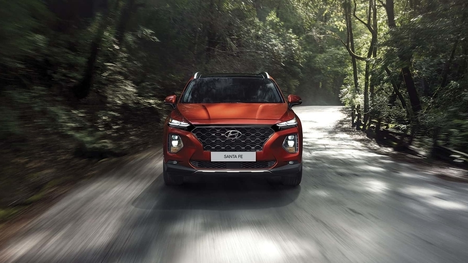 A front view of a red 2019 Hyundai Santa Fe expertly handling around the corner on a rural road