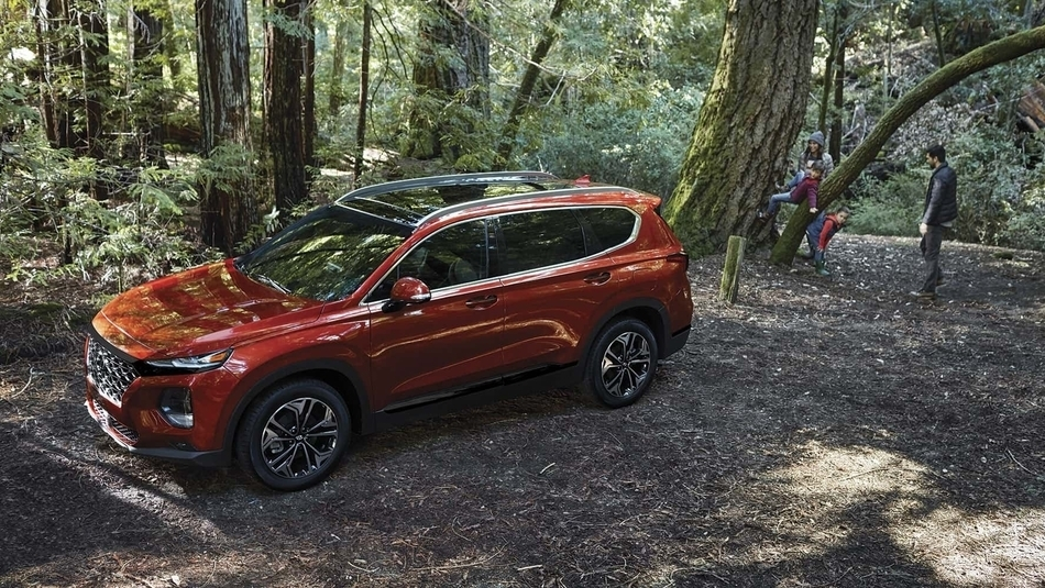 A red 2019 Hyundai Santa Fe parked at a campsite with a happy family playing in the trees behind it