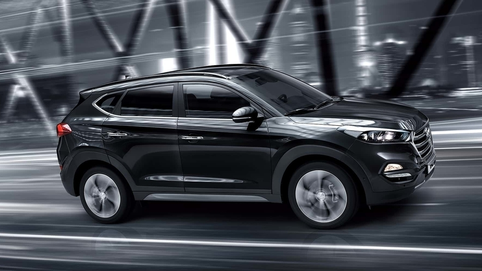 A black 2018 Hyundai Tucson driving along a bridge