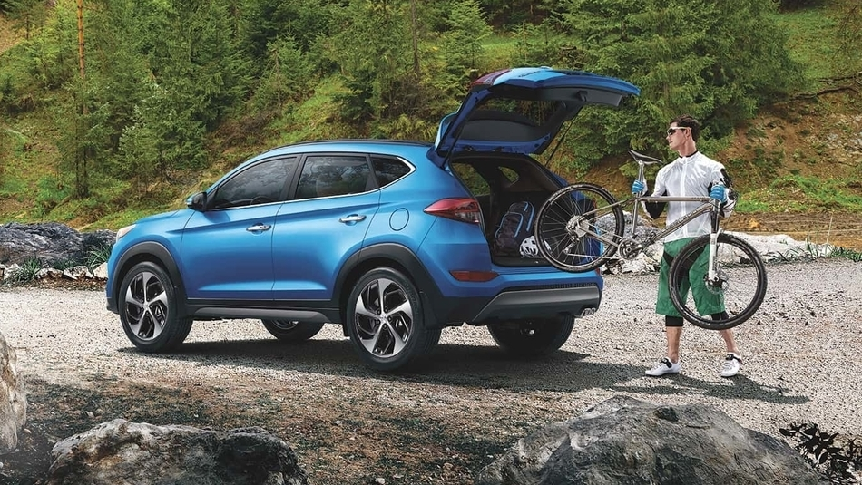 A man loads his bicycle into the rear cargo space of his blue 2018 Hyundai Tucson