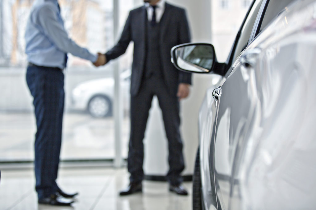 Handshake between two business people in a car showroom.