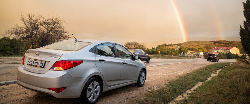 The car Hyundai Solaris (Accent) is parked in nature, with rainbow in the background