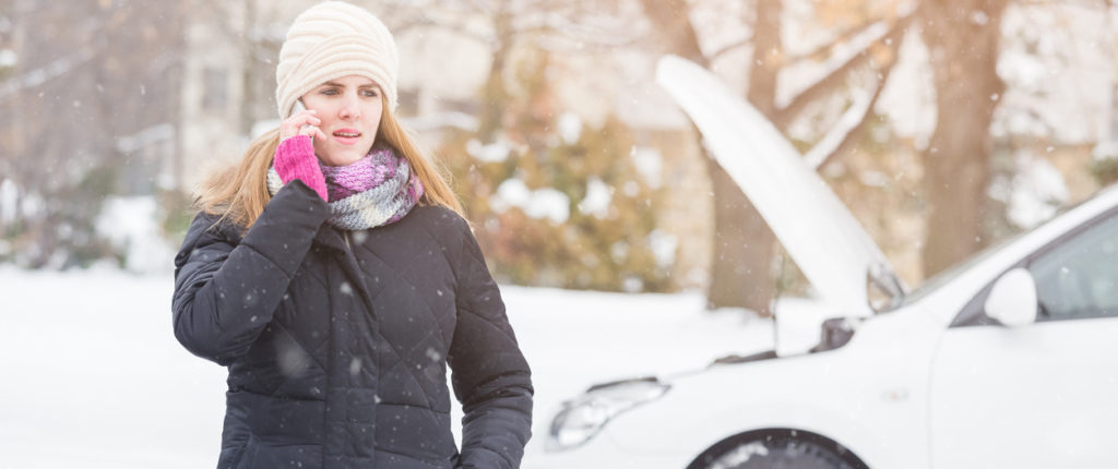 woman with broken down car on snowy road