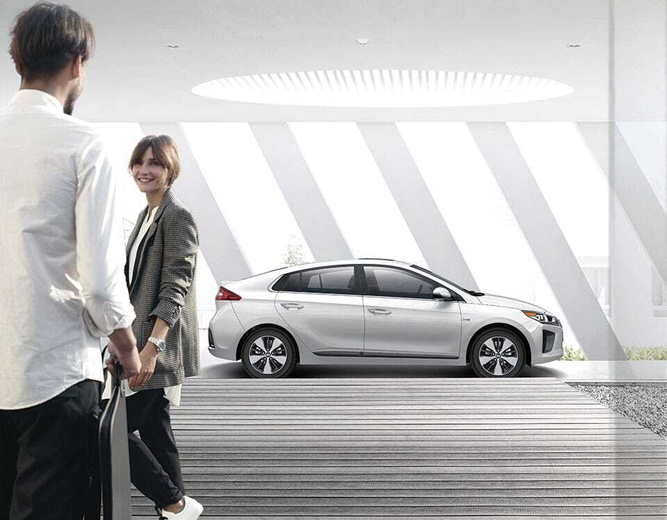 couple standing in foreground, with hyundai ev in background