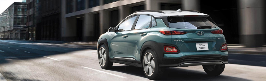 Rear 3/4 view of a 2019 Hyundai Kona Electric driving down the street