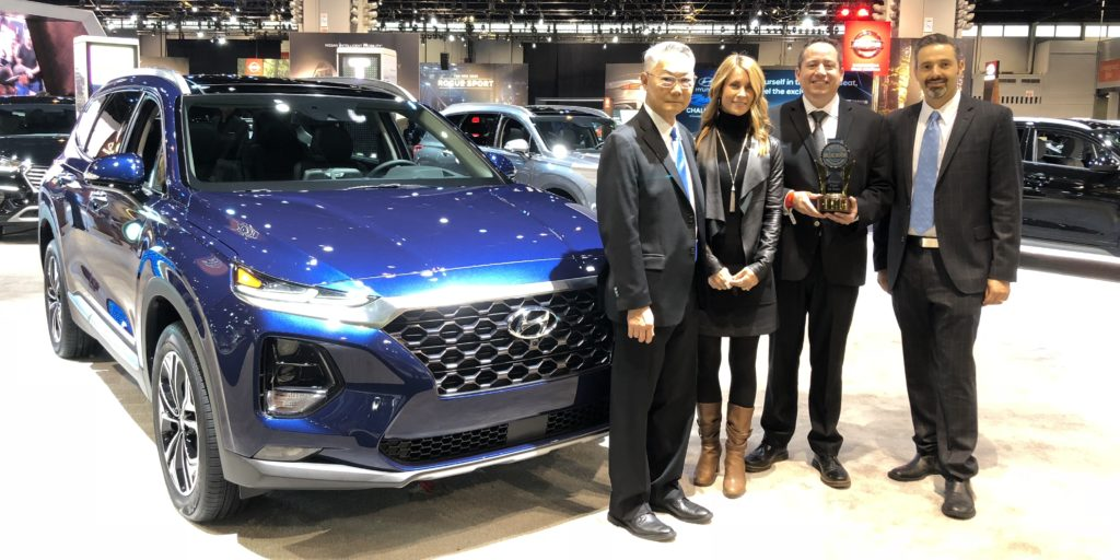 hyundai executives holding award in front of santa fe