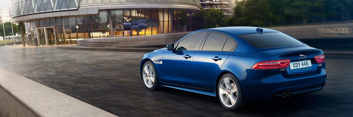 Blue Jaguar XE driving down London streets