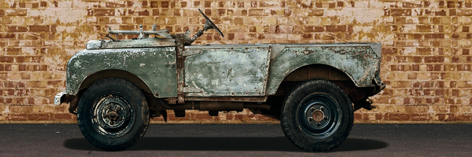 Sideview of a green army colour Land Rover Series I in front of a brown brick wall