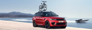 Red Range Rover drives shore-side with bike attached to roof rack, crystal blue skies and a speedboat passes by on the water