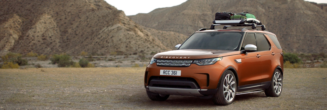 Orange Land Rover Discovery with camping equipment attached to the roof rack, large barren brown mountains in background
