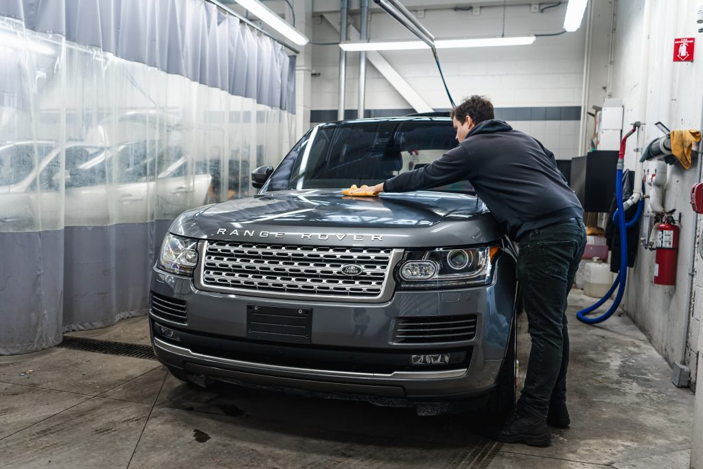 Front exterior view of a man detailing his Land Rover SUV