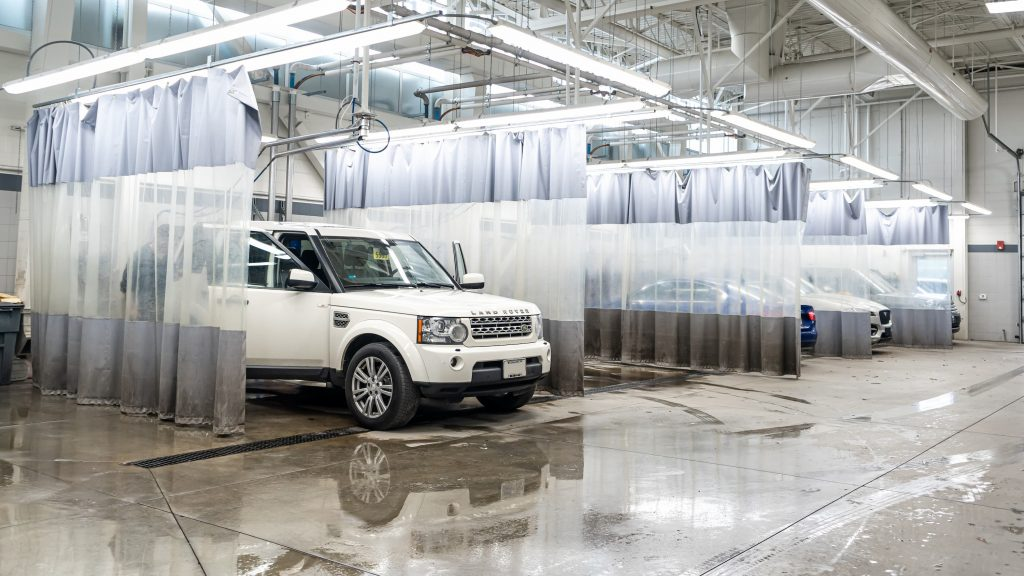 Front 3/4 exterior view of a Land Rover vehicle parked inside of the car wash