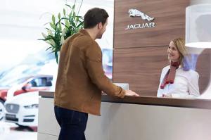 A customer greeted by a Jaguar staff representative at the concierge desk