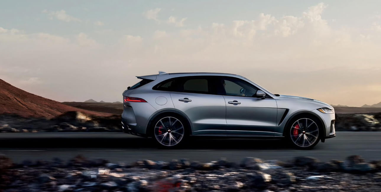 Side exterior view of the Jaguar F-Pace driving across the desert highway