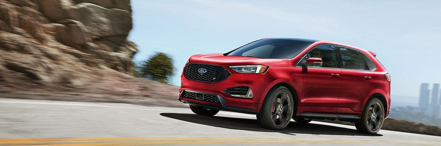 Red Ford Edge ST driving on highway next to rocky terrain
