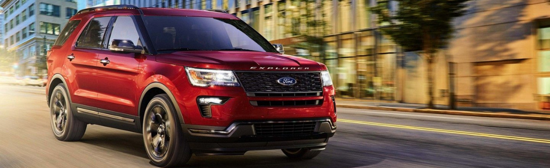 Front three-quarter passenger-side view of 2019 Ford Explorer Sport in Ruby Red on a city street at dusk