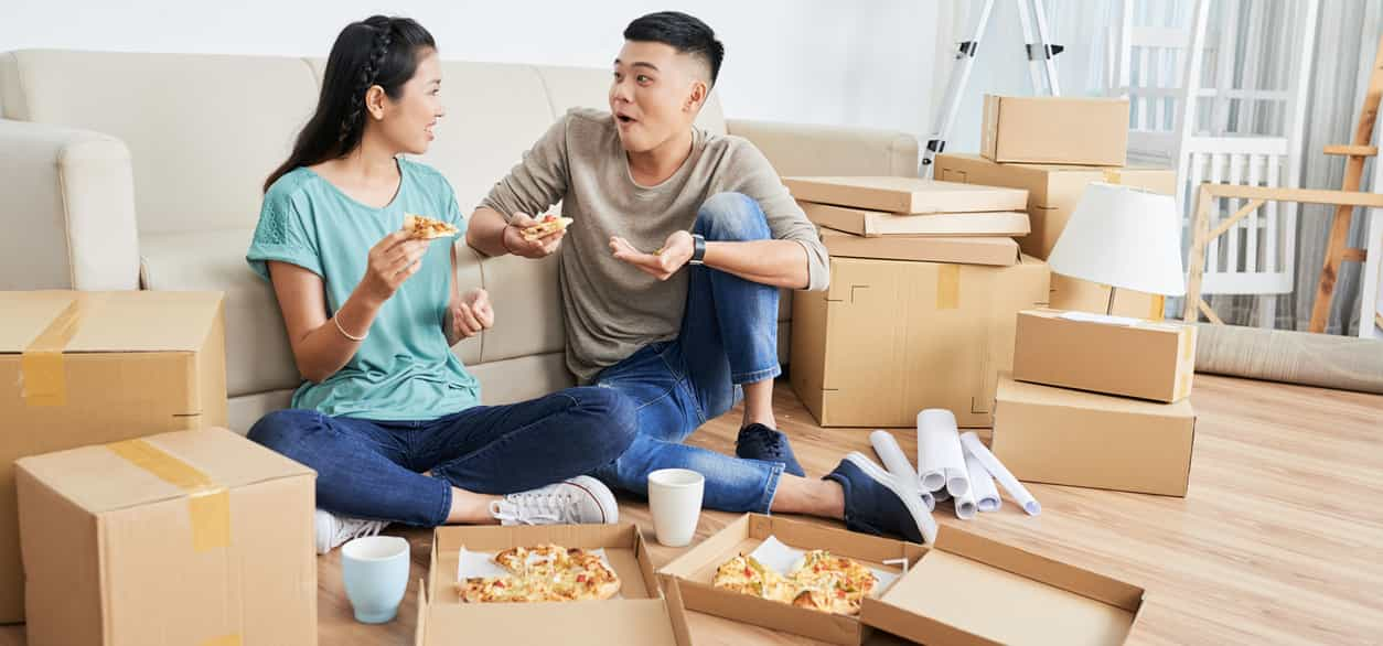 Asian couple eating pizza in new apartment