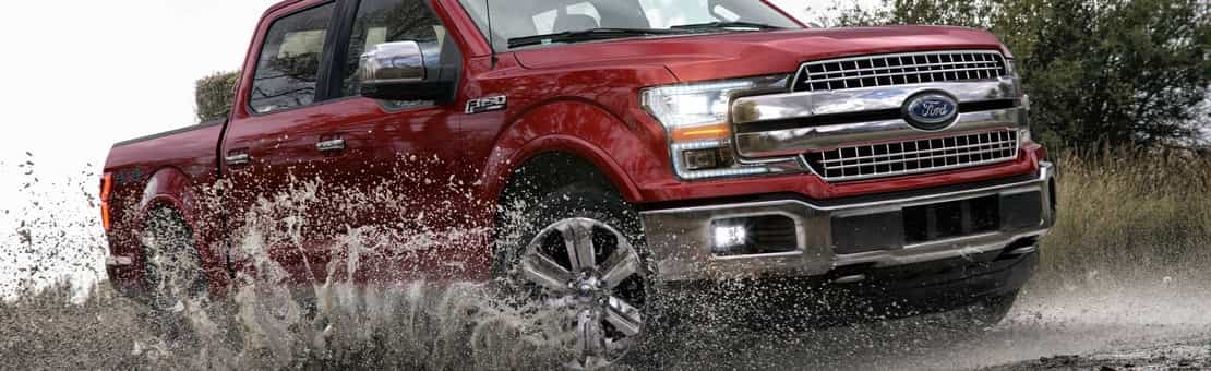 2019 F-150 Lariat SuperCrew in Ruby Red driving through dirty water