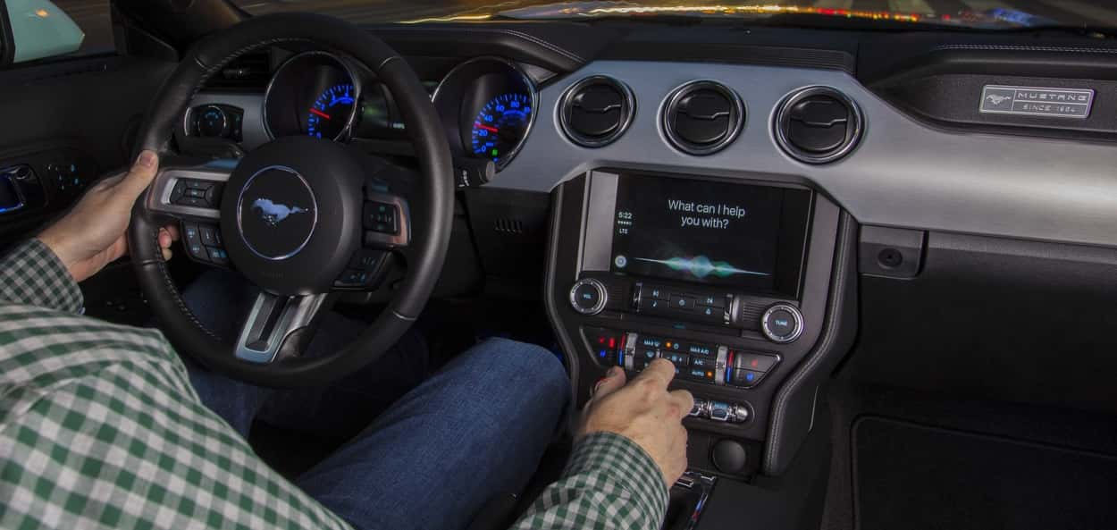 Interior of a Ford Mustang with the SYNC 3 system displaying the main interface for Apple CarPlay