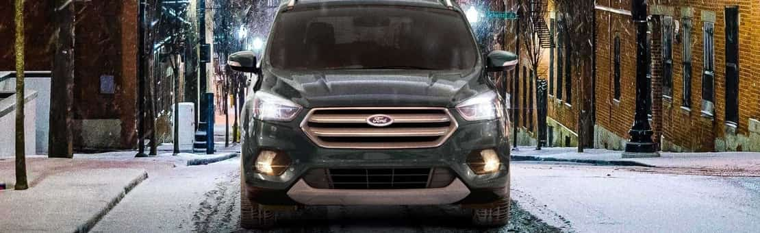 2019 Ford Escape in black parked in the dark with a snowy background and the LED headlights flashing towards the front