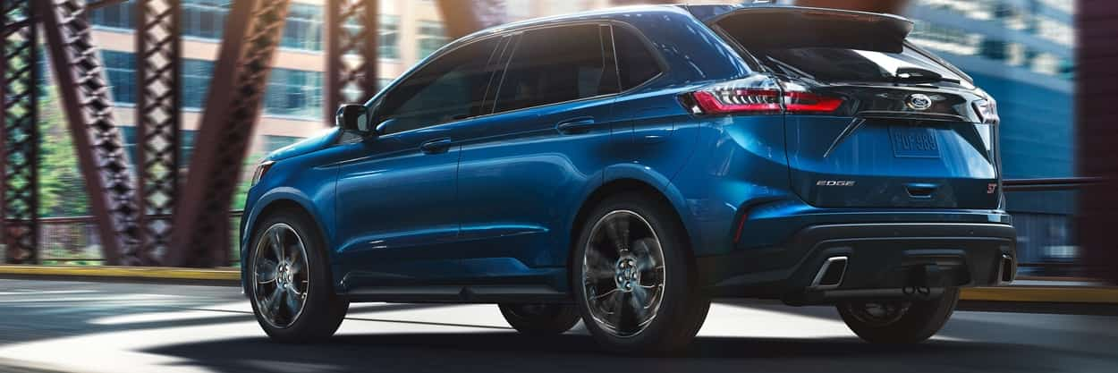 2019 Ford Edge ST in Ford Performance Blue driving down a bridge