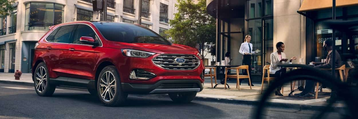 2019 Ford Edge Titanium sown in Ruby Red parked outside a city restaurant
