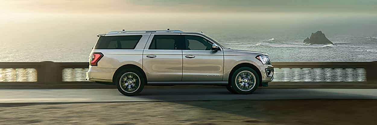 2019 Ford Expedition Platinum shown in White Platinum Metallic Tri-Coat driving near a beach