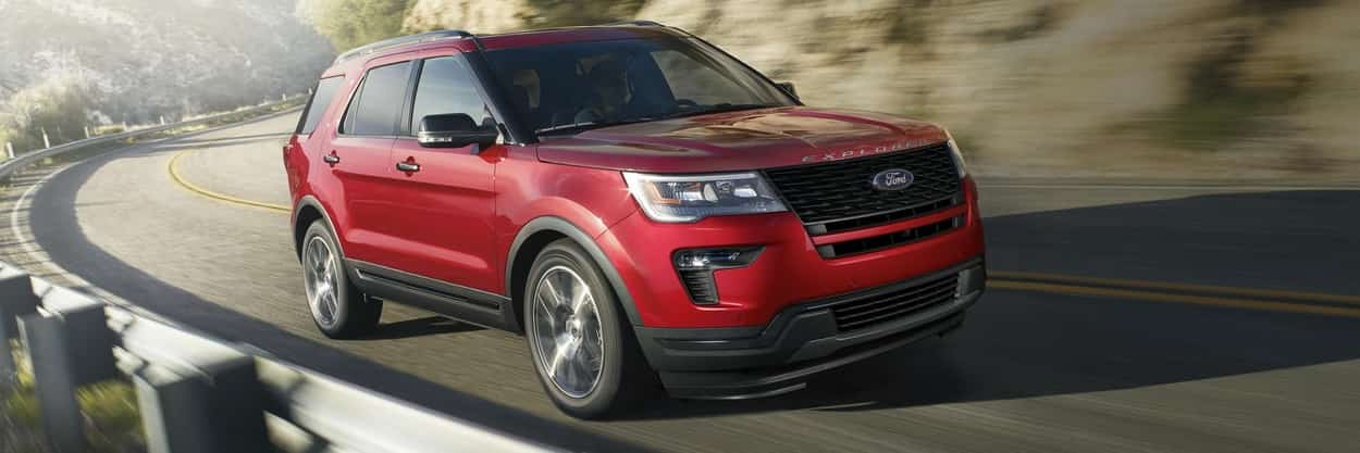 2019 Ford Explorer Sport in Ruby Red Metallic Tinted Clearcoat driving on a curved road