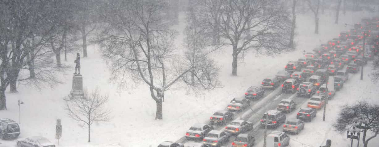 A bunch of cars at a stand still in winter