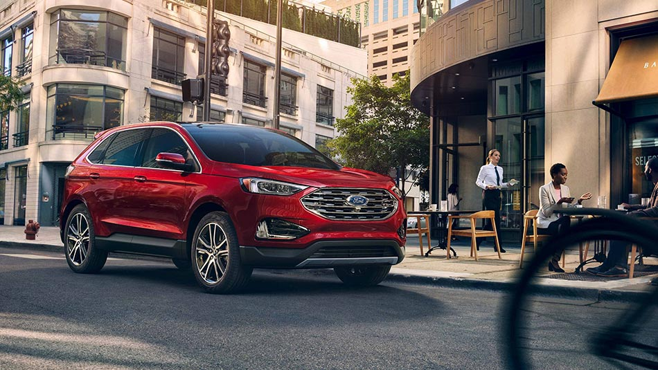 2019 Ford Edge driving down city street 3/4 view