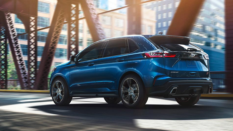 2019 Ford Edge ST driving over city bridge rear 3/4 view