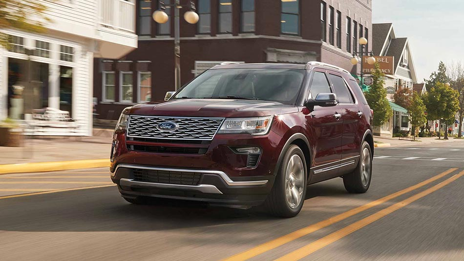 2019 Ford Explorer driving on city street front 3/4 view