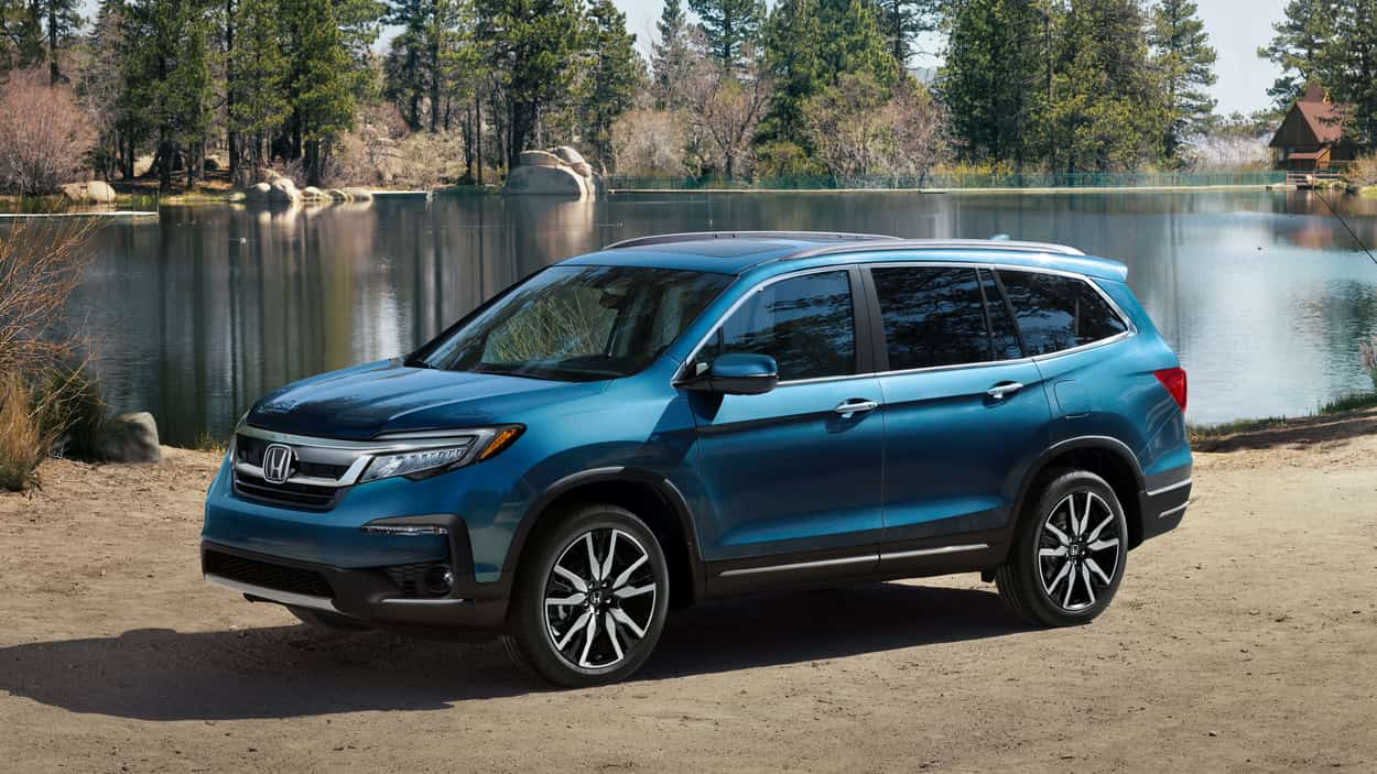 2019 honda Pilot in blue parked in front of a lake