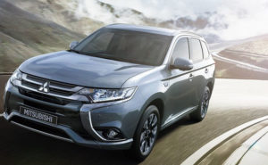 Mitsubishi Outlander PHEV driving away from the sun on a mountain highway