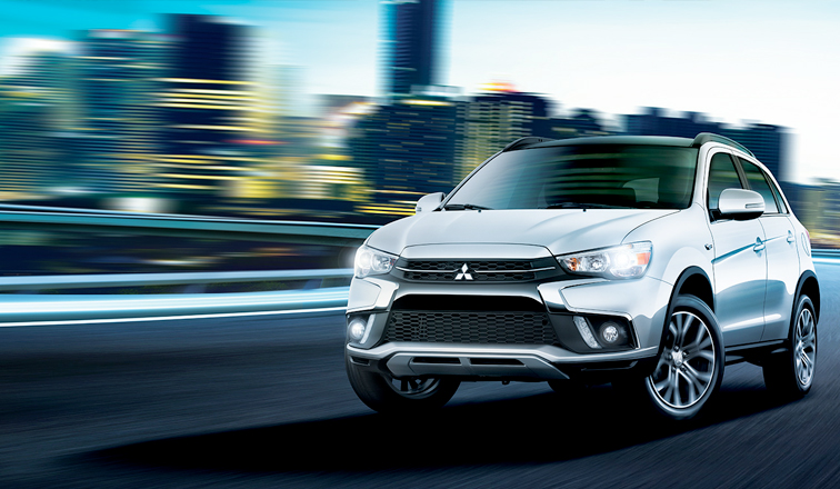 Mitsubishi RVR in grey driving with the background blurred out