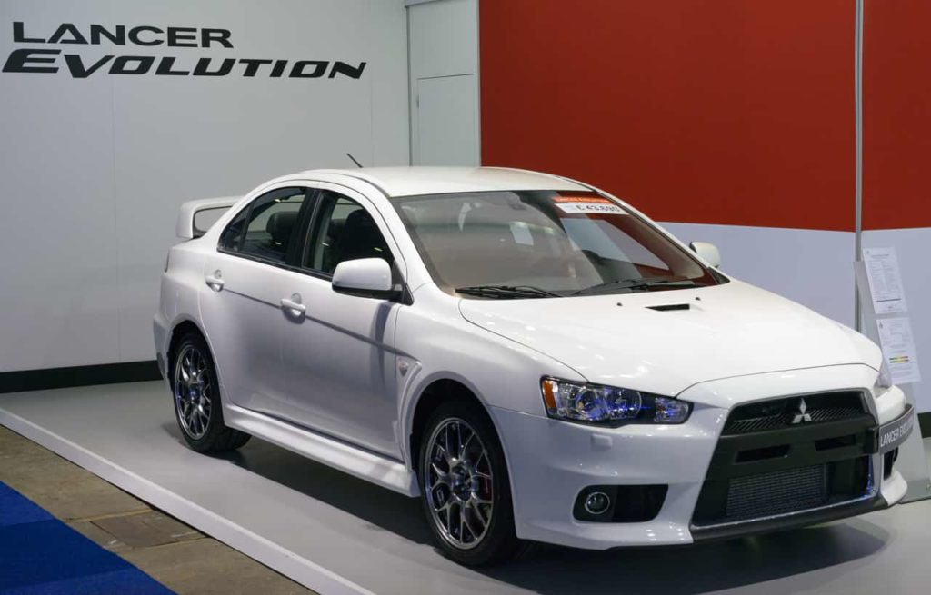 A 2014 Mitsubishi Lancer Evolution in white parked infront of a banner with the vehicle's name