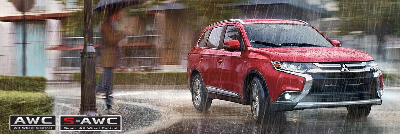 Mitsubishi Eclipse Cross driving in the rain with the AWC and S-AWC logos on the bottom left corner of the grahpci