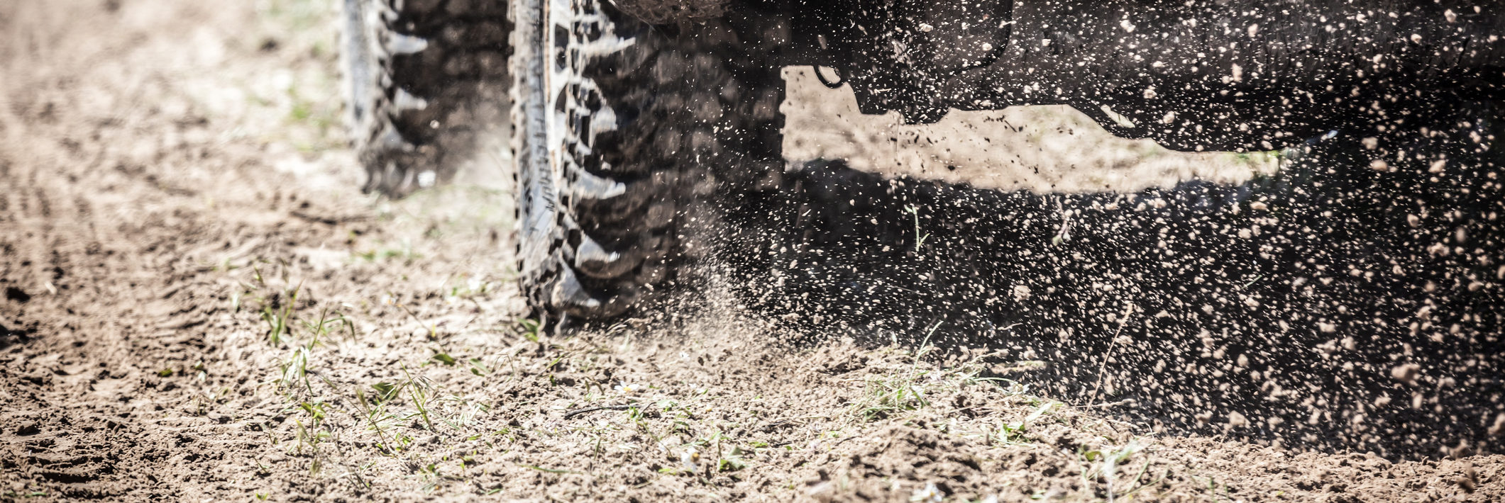 Tires of an off-road racing car zipping along a country road.