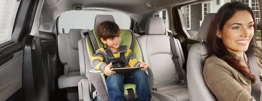 Honda Odyssey Interior, a child in the 2nd row and a woman in the drivers seat