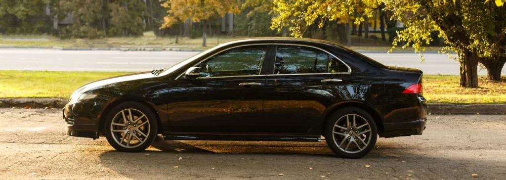 Honda Accord dark color on the walkway of Dnipro city street, autumn time. Cityscape on sunset